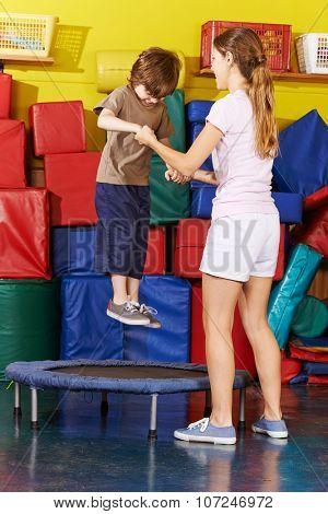 Happy boy jumping on trampoline in kindergarten in gym