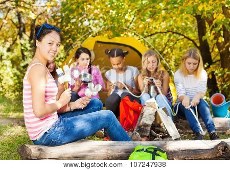 Asian girl holds sticks with s'mores sitting