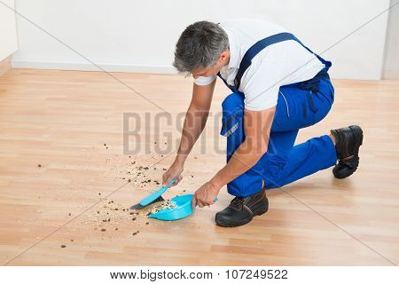Janitor Sweeping Floor With Brush And Dustpan