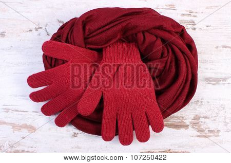 Pair Of Woolen Gloves And Shawl For Woman On Old Wooden Background