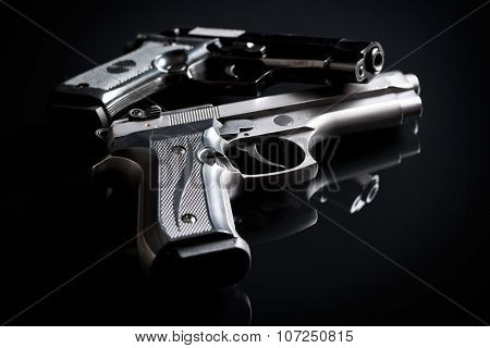two handguns on black background