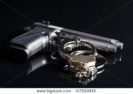 handcuffs and handgun on black background
