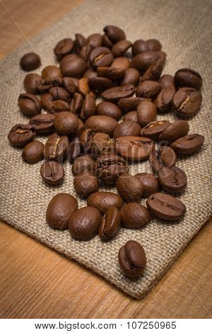Heap Of Coffee Beans On Jute Canvas On Table