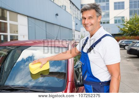 Happy Male Worker Cleaning Car Windshield With Sponge