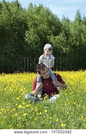 Happy Father With His Daughter On Shoulders Among Yellow Flowers At Meadow At Summer Day