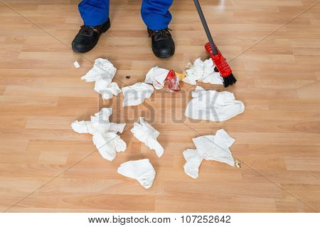 Janitor Sweeping Crumpled Papers On Floor