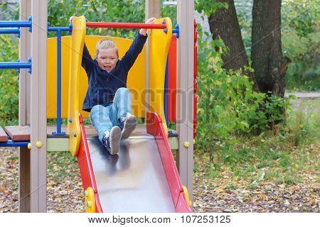 Handsome Little Boy Plays On Slide On Playground In Autumn Day