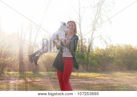 Happy Young Mother Plays With Her Little Daugther At Sunny Autumn Day