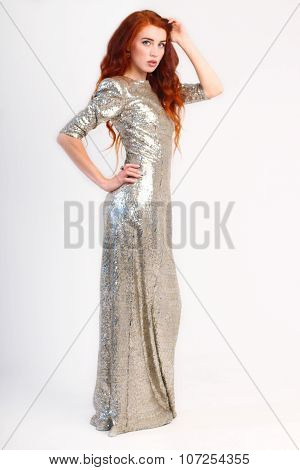 Beautiful Girl With Red Hair And Shiny Silver Dress In Studio. Full Body View