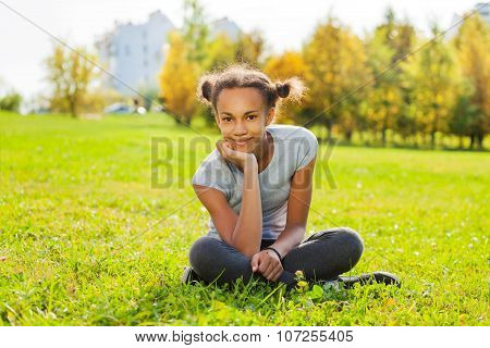 Portrait of African girl sitting on green grass