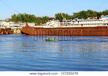 Man And Woman Sail On Motorboat Near Old Rusty Ship On River At Summer Day