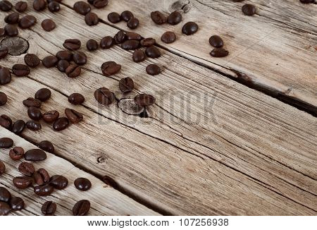 Spilled Coffee Beans On Wooden Table Closeup