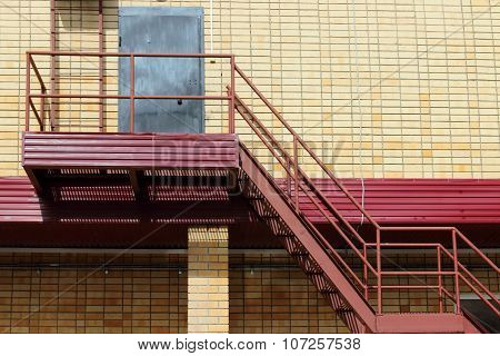 Part Of Modern Building - Yellow Brick Wall, Door And Red Metal Stairs