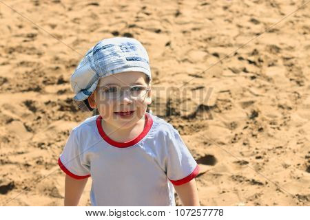 Little Handsome Boy In Cap And Glasses Smiles On Sand At Summer Day
