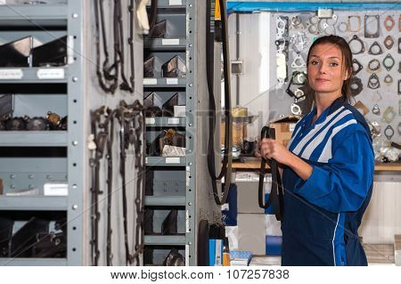 Female mechanic with a distribution belt in her hands in the storage room of a garage, filled with shelfs and racks with spare parts for car maintenance