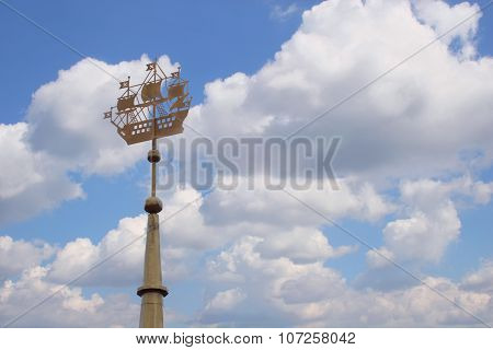 Closeup Spire Of Building With Metal Sailing Ship Against Blue Sky With Clouds