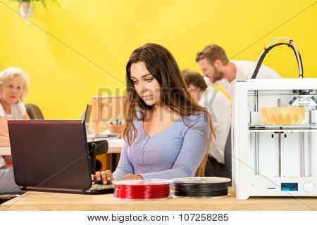 Young female designer using laptop by 3D printer with colleagues in background at studio