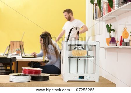3D printer with products on counter with designers working in background at creative studio
