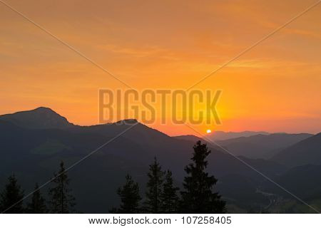 View of the sky turning orange, red during sunset behind mountain ranges in Europe. Focusing on Pine trees