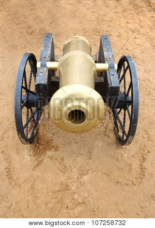 Old Yellow Metal Cannon With Black Wheels On Sand Outdoor At Summer
