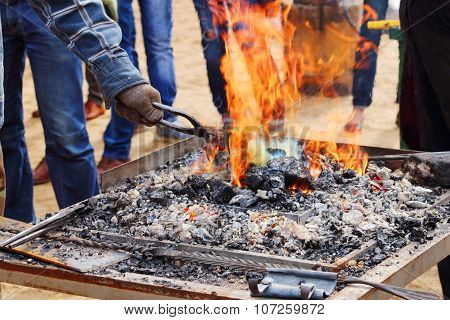 Burning Coals With Bright Orange Flame And Hand Of Blacksmith With Tongs