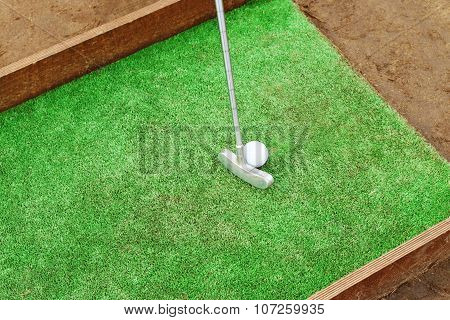 Artificial Lawn, Putter And Golf Ball On Wooden Stand For Training
