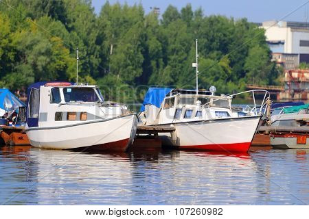 Small Modern Motorboats At Pier On River At Summer Sunny Day