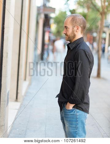 Man in his thirties looking at a shop window