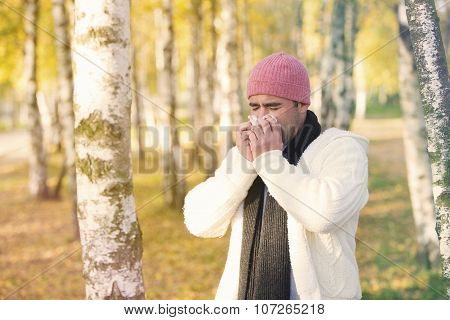 Man In Park Blowing His Nose