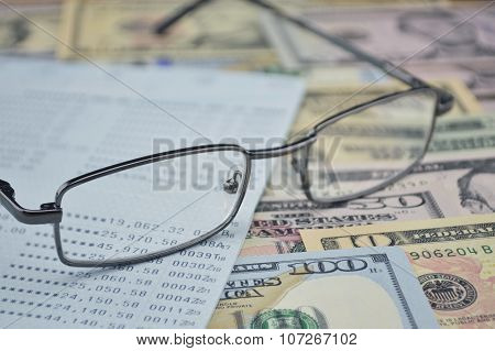 Glasses And Account Book On Dollar Bank Note