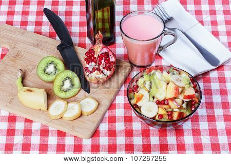 Fruit Salad, A Bowl Of Dark Glass, Cutting Board, Cut Fruit, Olive Oil, Knife, White Napkin, Fork On