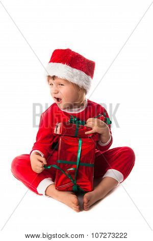 Funny Child In Santa Red Hat Holding Christmas Gift In Hand. Christmas Concept.