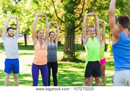 fitness, sport, friendship and healthy lifestyle concept - group of happy teenage friends or sportsmen exercising and stretching hands up at boot camp