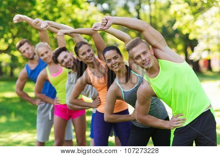 fitness, sport, friendship and healthy lifestyle concept - group of happy teenage friends or sportsmen exercising and stretching at boot camp
