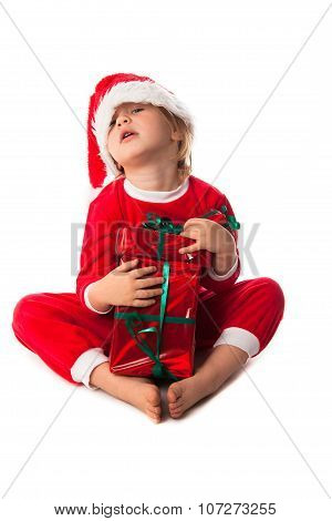 .greedy, Harmful  Child In Santa Red Hat Holding Christmas Gifts In Hand. Christmas Concept.