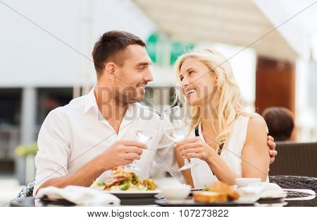 love, dating, people and holidays concept - smiling couple clinking glasses and looking to each other at restaurant lounge or terrace