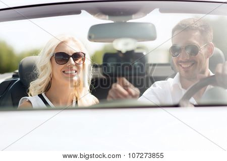 road trip, leisure, travel, technology and people concept - happy man and woman driving car and using gps navigation system