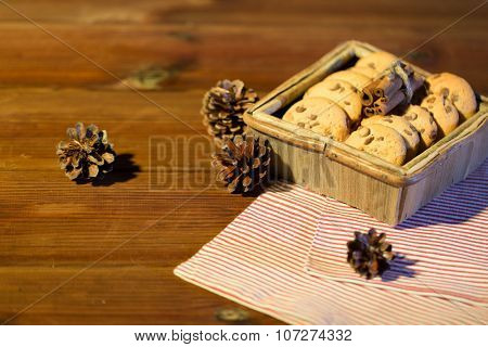 christmas, baking, culinary, holidays and food concept - close up of oat cookies in wooden box with cinnamon and pinecones on table