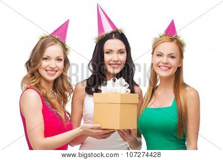 celebration, friends, bachelorette party, birthday concept - three smiling women wearing pink hats with gift box