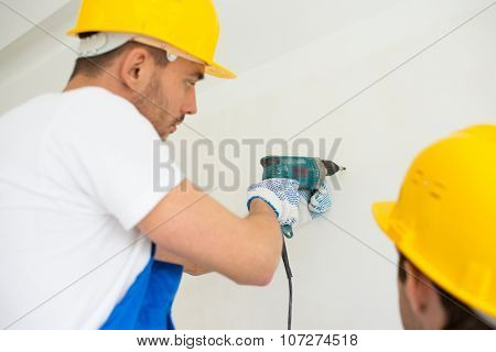 building, teamwork, working equipment and people concept - close up of builders with electric drill perforating wall indoors