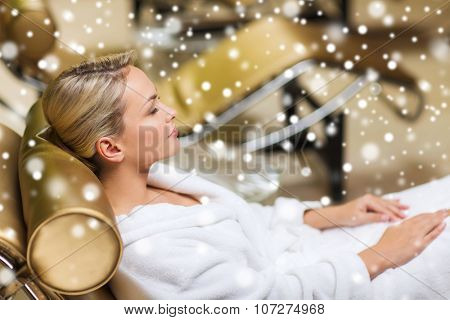 people, beauty, healthy lifestyle and relaxation concept - beautiful young woman lying on chaise-longue in bath robe at spa with snow effect