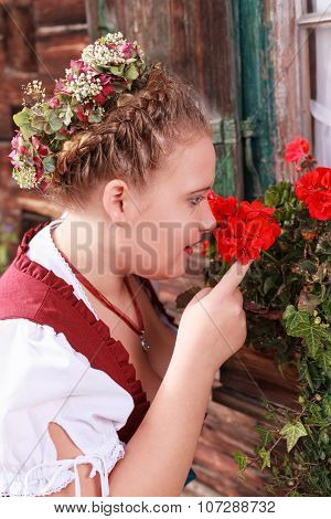 Portrait of a young woman in dirndl smell of a geranium
