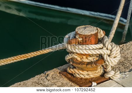 Ship rope tightly bound to the rusty quay.