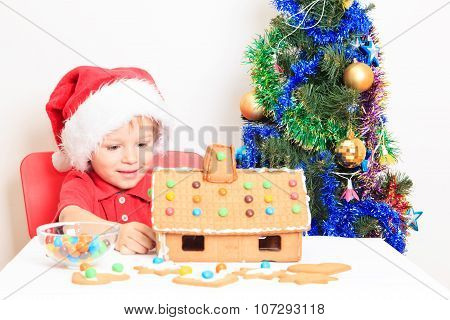 Smiling boy in Santa's hat with gingerbread house