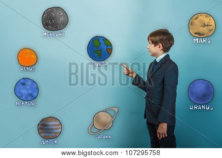 Teen boy businessman in a suit specifies hand on the planets of