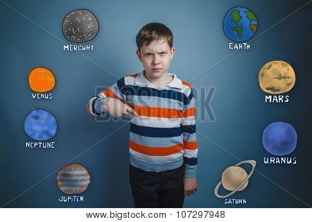 Teen boy frowned dissatisfied points a finger down the planets o