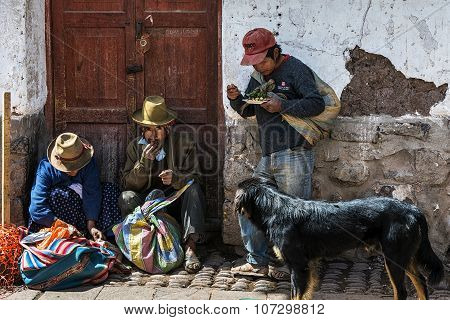 Locals eating in the street in a market in the city of Pisac in the Sacred Valley.