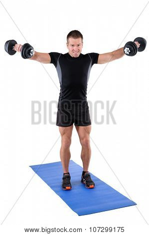 young man fitness instructor shows finishing position of standing dumbbell lateral raise, isolated on white