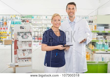 Portrait of smiling female assistant using digital tablet while male pharmacist holding product in pharmacy
