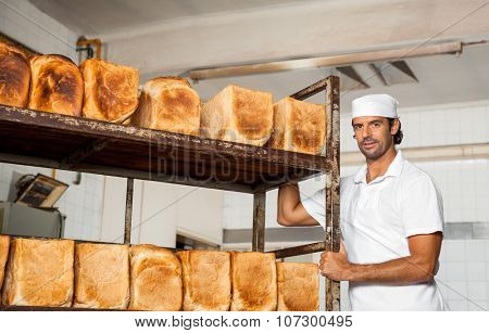 Portrait of confident mid adult male baker standing by bread rack in bakery